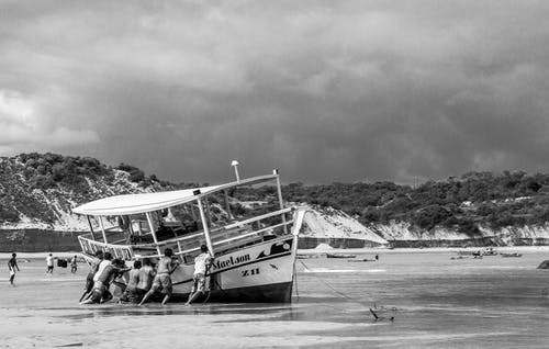 Grayscale Photo of People Riding on Boat on Sea