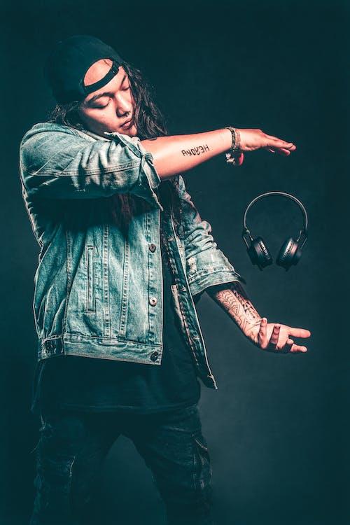 Man in Blue Denim Jacket Floating Black Headphones