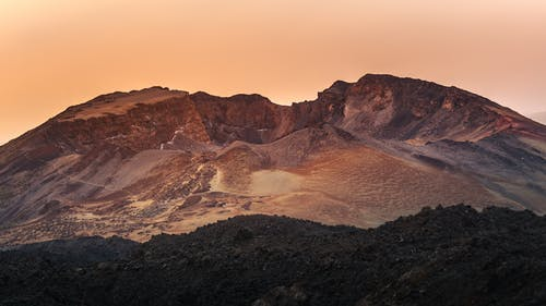 Brown Rocky Mountain Under Orange Sky