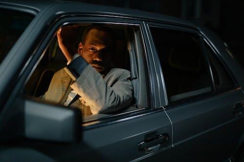 Man in Gray Jacket Sitting on Car Seat