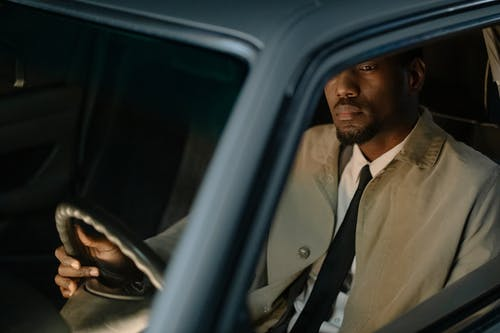 Man in White Dress Shirt Driving Car