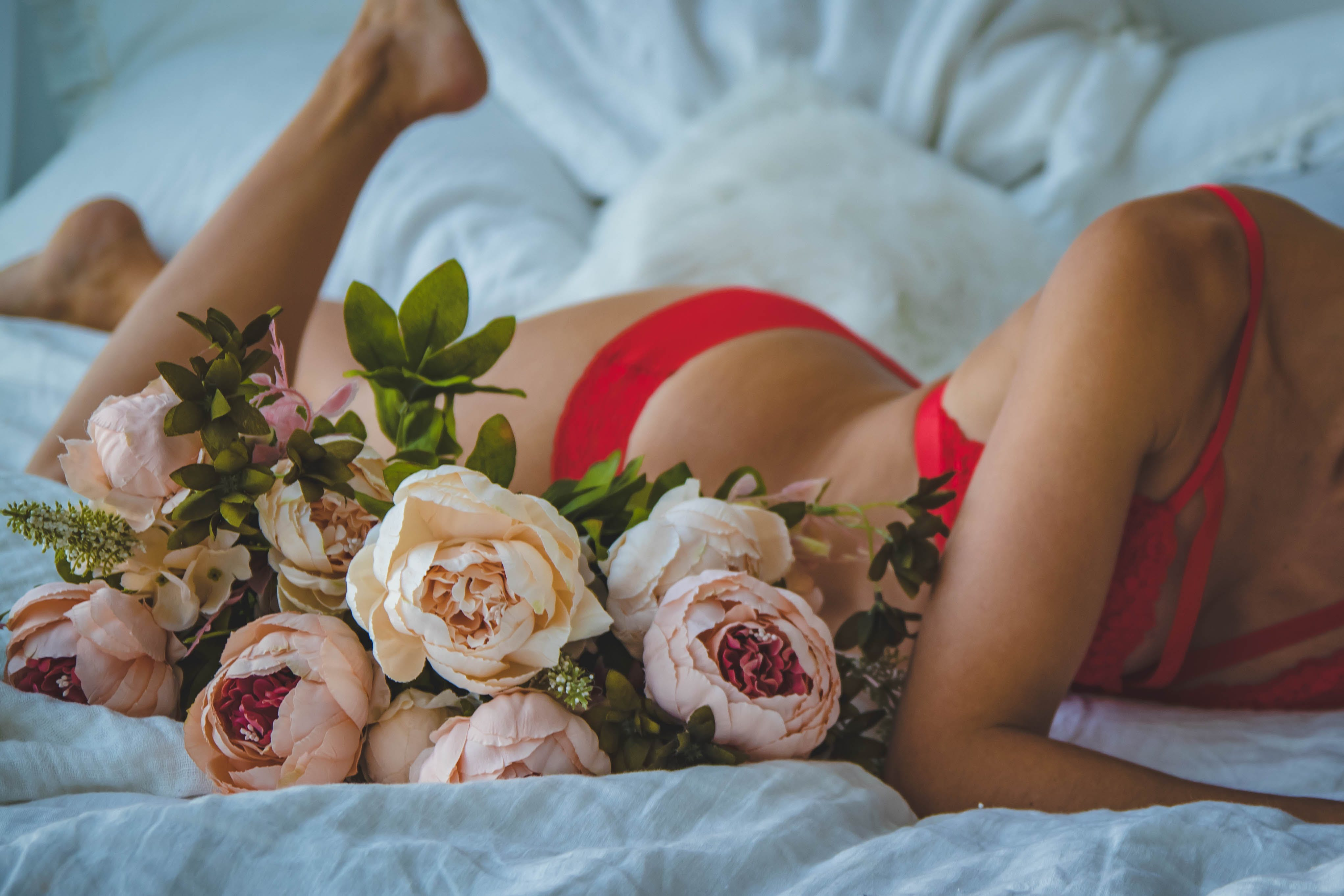 Woman in Red Two-piece Bikini Lying on Bed Beside of White and Pink Roses