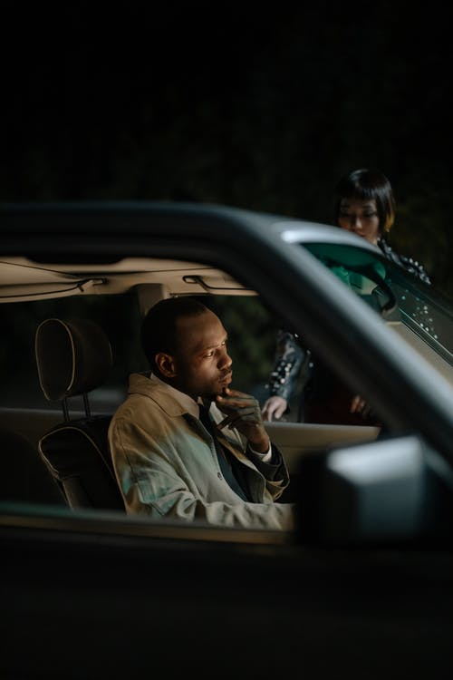 Man in Brown Coat Driving Car
