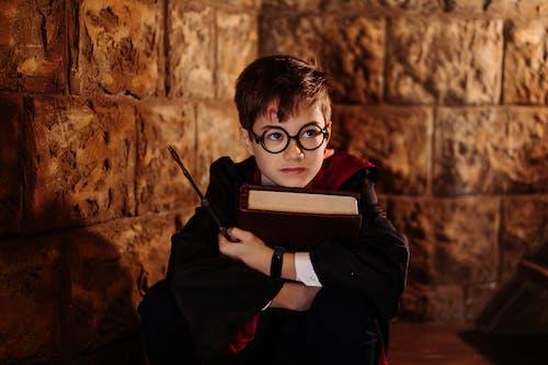 Boy in Black Framed Eyeglasses Reading Book