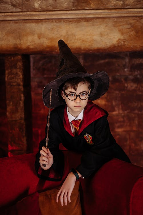 Boy Wearing a Witch Hat while Holding a Wand