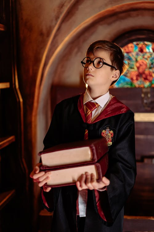 A Boy in Harry Potter Costume Carrying Books