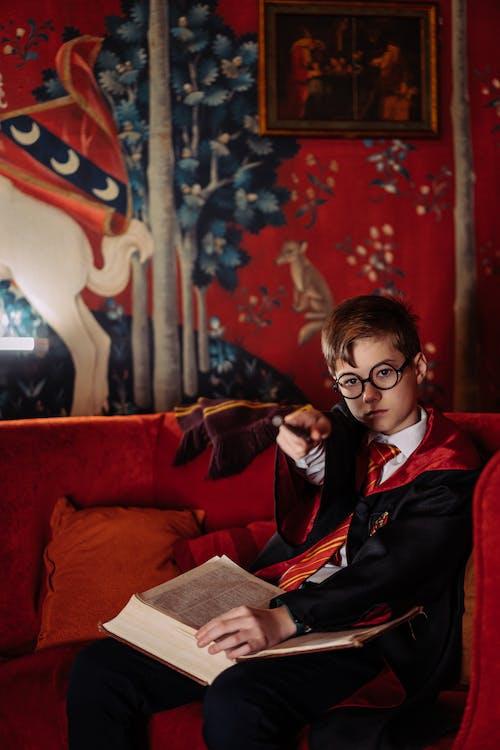 Woman in Black Blazer Sitting on Red Sofa