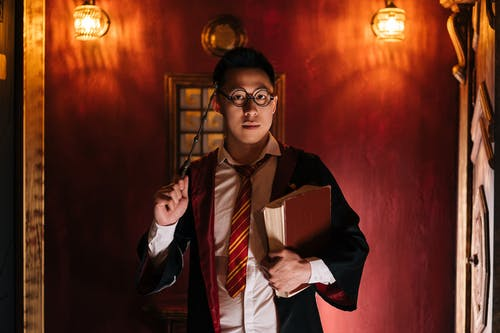 Man Holding a Book and Wand