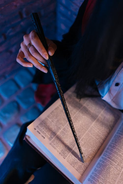 Person Holding a Book and Wand