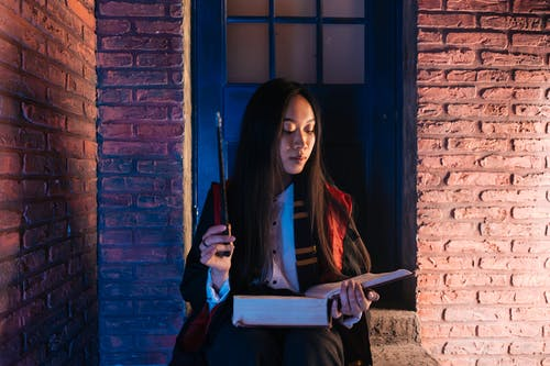 Woman Holding a Book and Wand