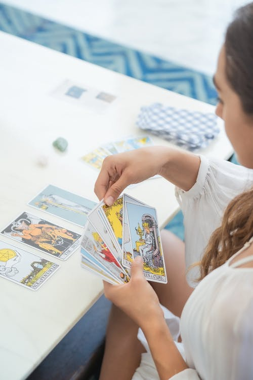 Person Holding a White and Blue Floral Print Cards