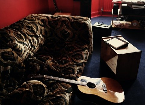 Brown Acoustic Guitar Leaning on Brown Velvet Couch