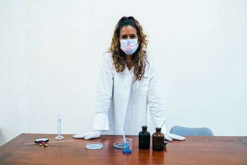Woman in White Coat Standing Beside Brown Wooden Table