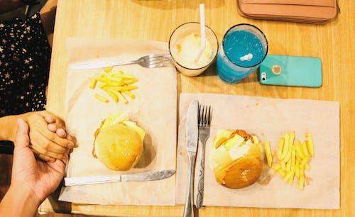 Gratis arkivbilde med burger, en, hender, juice
