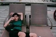Man Wearing Green Shirt and Black Shorts Laying on Lounger