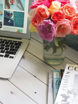 Assorted-color Flower Arrangement in Clear Glass Vase Beside a Laptop