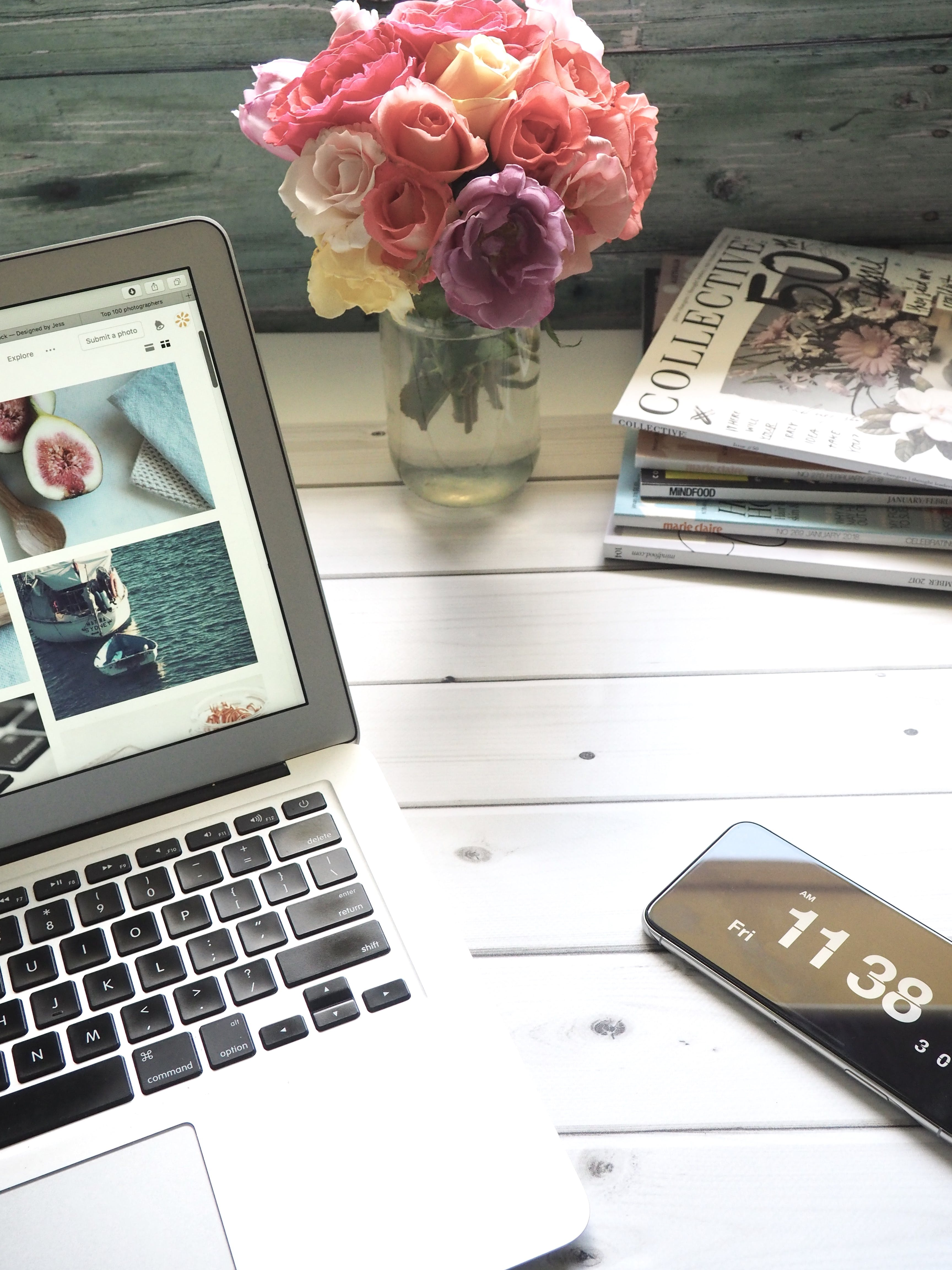 Macbook Air, Flower Bouquet and Magazines on White Table