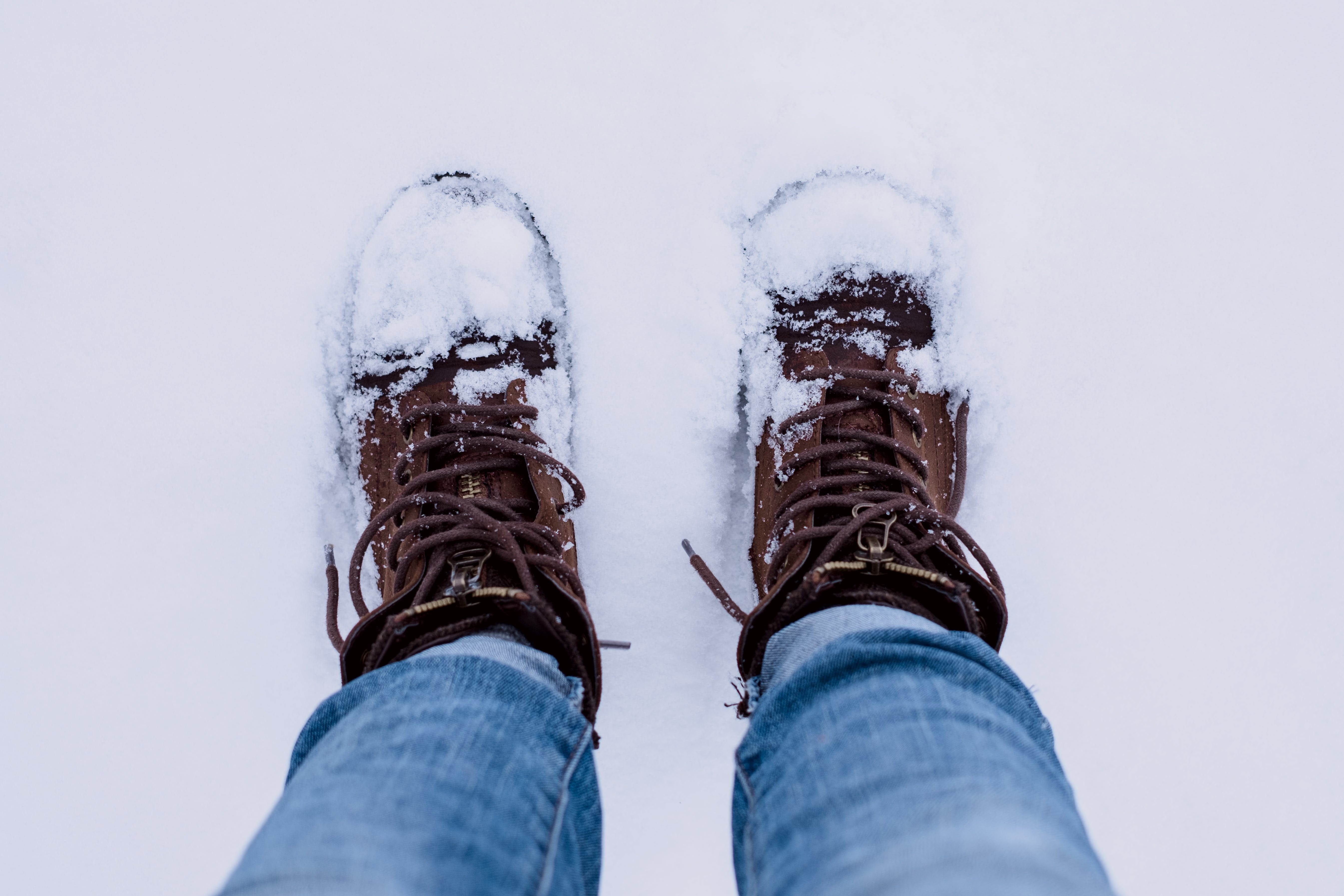Person Wearing Brown Boots and Blue Denim Jeans Standing on Snow