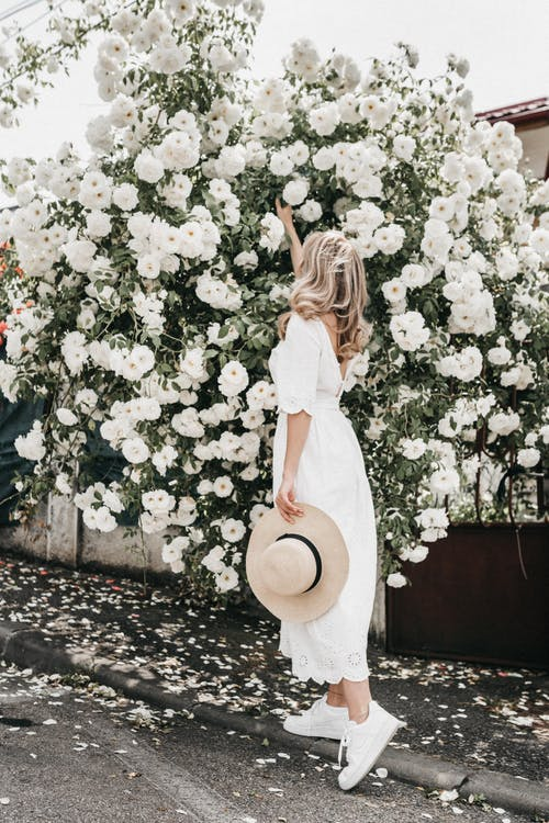 Woman in White Dress Standing Near White Flowers