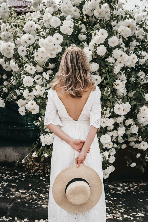 Woman in White Dress Holding Brown Hat