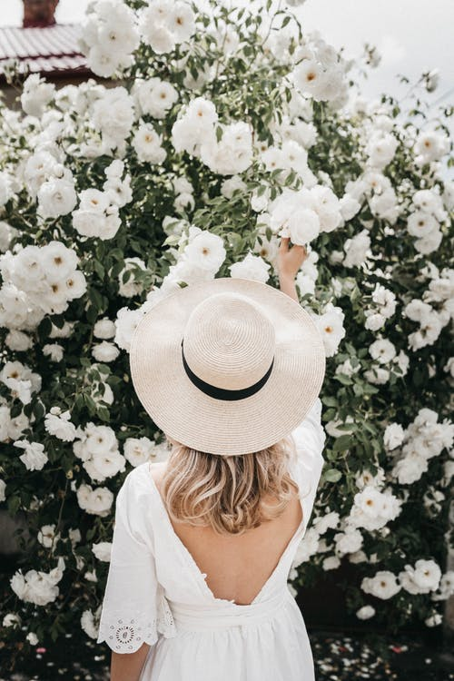 Woman in White Shirt and White Sun Hat Standing Beside White Flowers