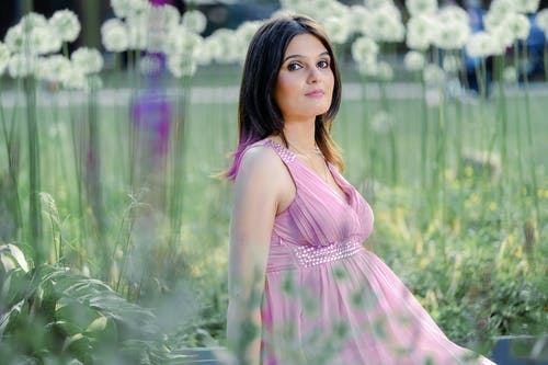 Woman in Pink Sleeveless Dress Standing on Green Grass Field