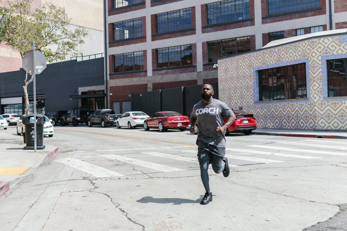 A Man in Activewear Jogging on the Street