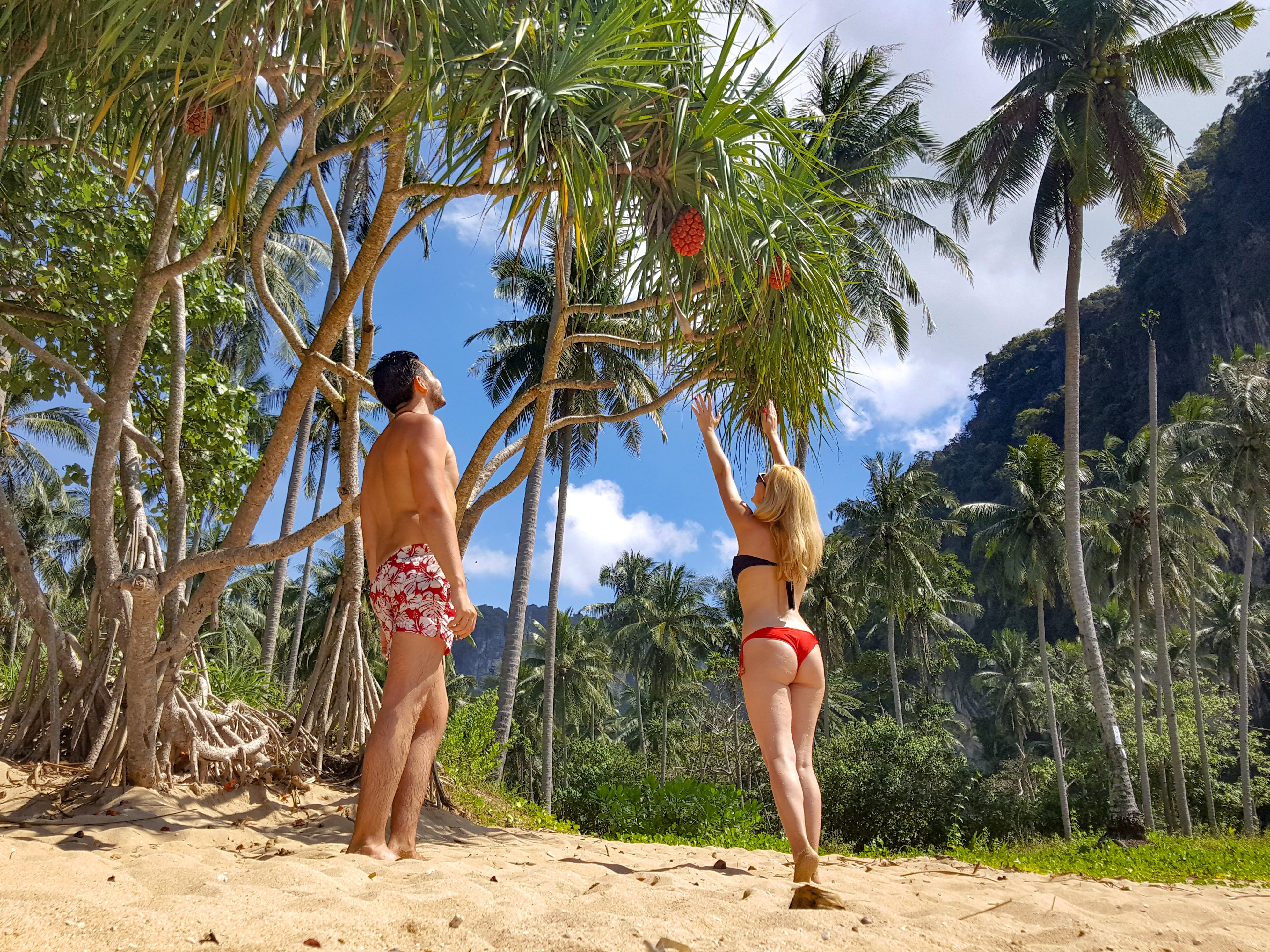 Woman Wearing Black Bikini Top and Red Bottom Beside Man Wearing White and Red Floral Shorts