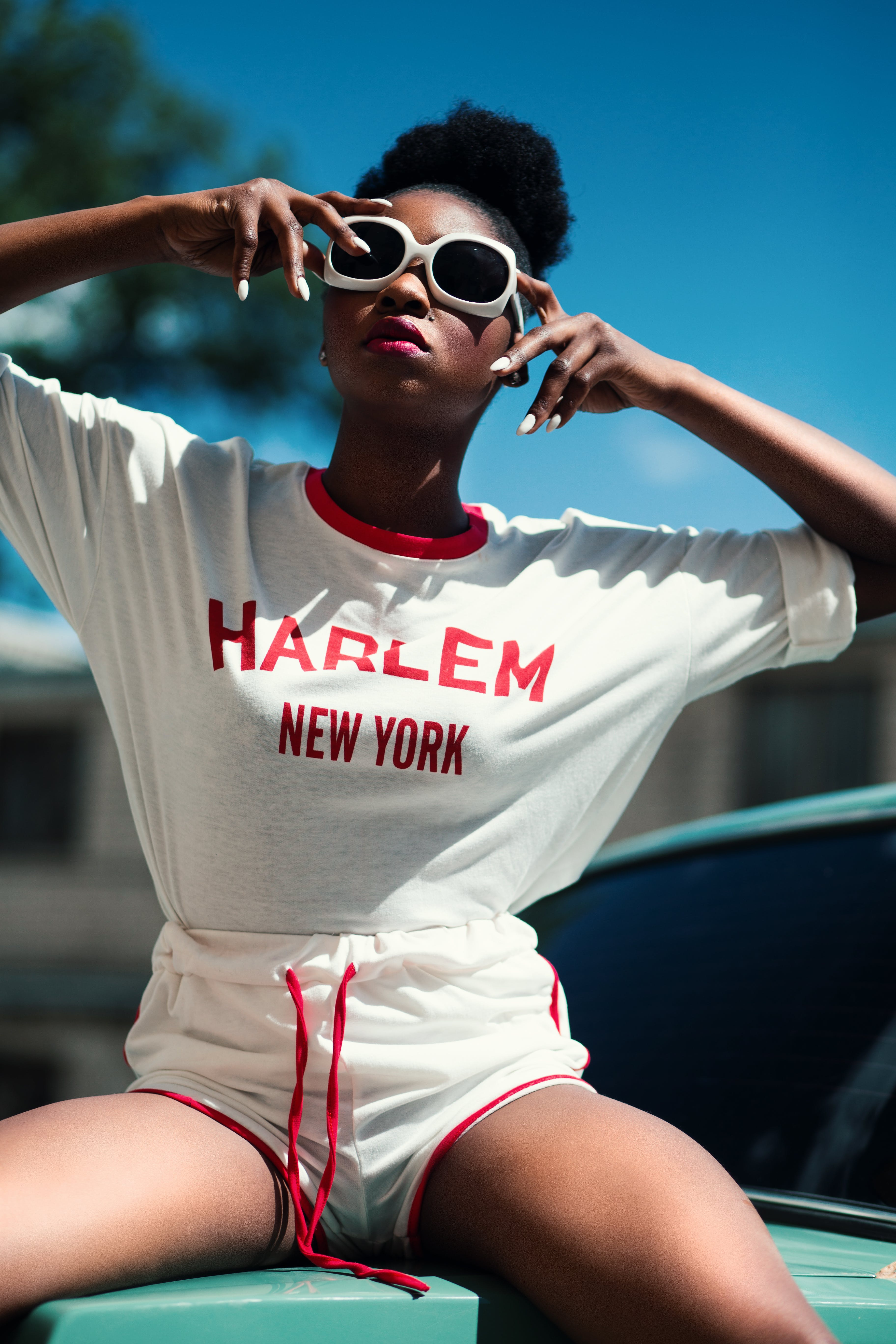 Woman Wearing White and Red Harlem New York Printed Round-neck Batwing-sleeved Shirt With Drawstring Dolphin Shorts