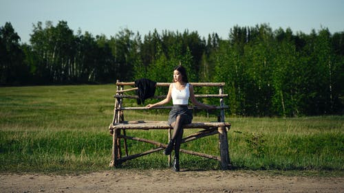 Woman in White Tank Top Sitting on Brown Wooden Bench
