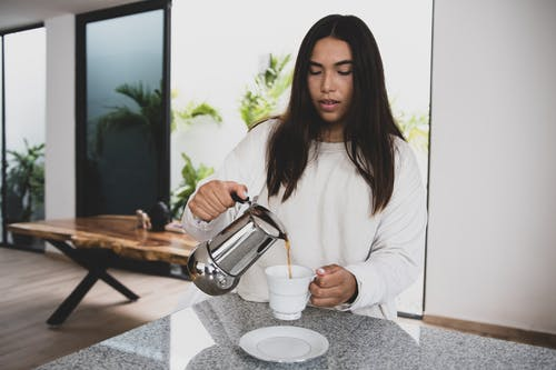 Woman in White Long Sleeve Shirt Holding Stainless Steel Teapot Pouring Water on White Ceramic Cup