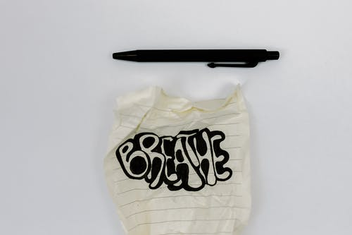 White and Black Plastic Bag Beside Black Pen