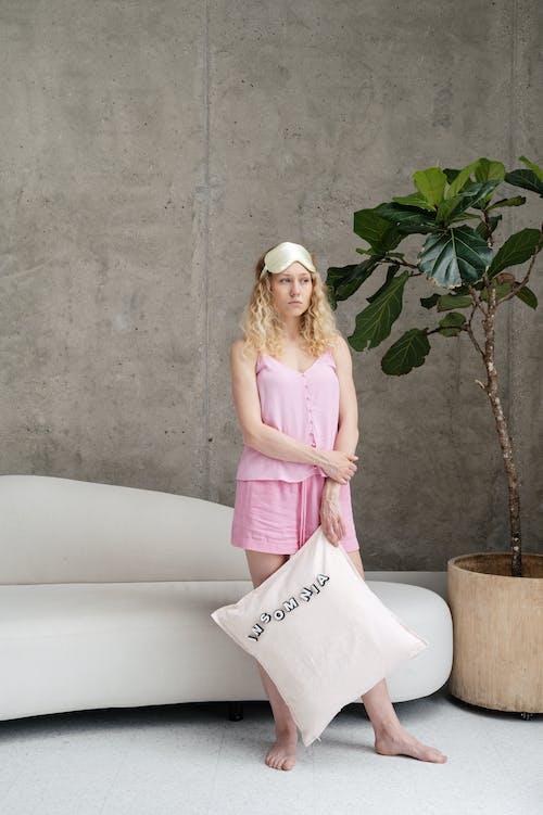 Woman in Pink Sleeveless Sleepwear Holding a Pillow
