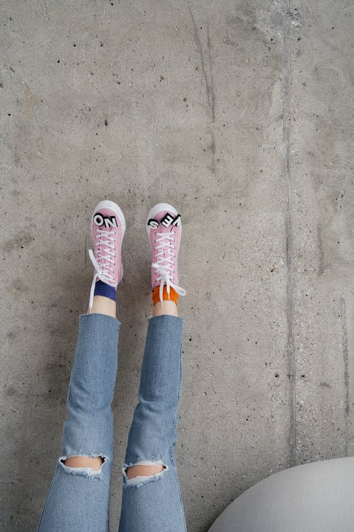 Person in Blue Denim Jeans and Pink Sneakers