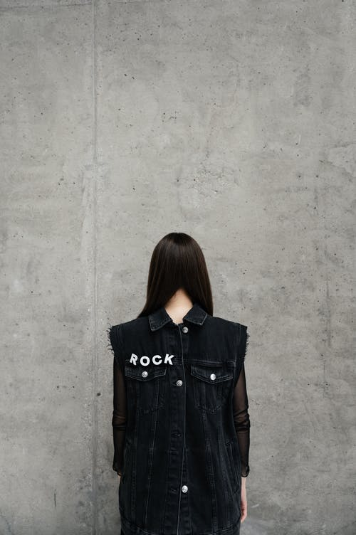 Person with Black Hair Wearing a Denim Vest