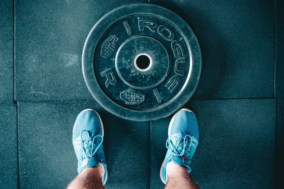 Black Steel Gym Plate and Pair of Blue Running Shoes
