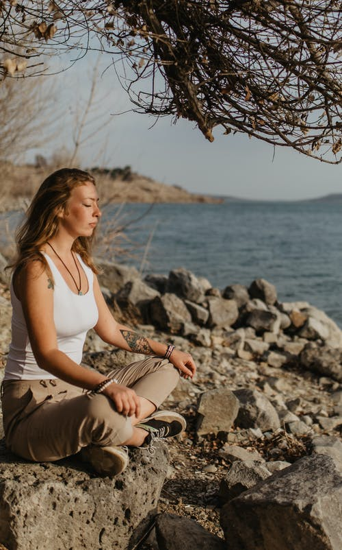 Young relaxed woman sitting on rocky lake shore in Padmasana pose with closed eyes