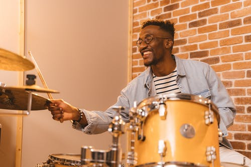 A Man in Denim Jacket Playing Drums