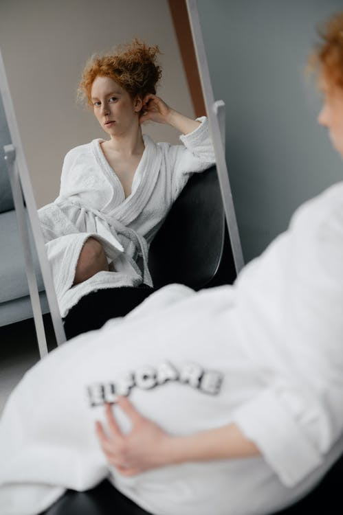 Woman in White Robe Sitting In Front of a Mirror