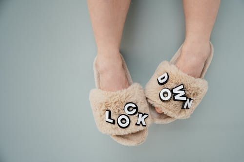 Person Wearing Brown House Slippers