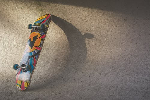 Multicolored Skateboard Leaning on Wall