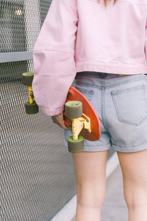 Person in Pink Jacket and Blue Denim Shorts Holding Orange and Yellow Plastic Toy Gun