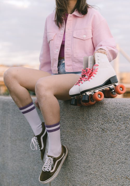 Woman in Pink Blazer and Black Shorts Sitting on Concrete Pavement
