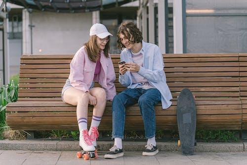 2 Girls Sitting on Brown Wooden Bench