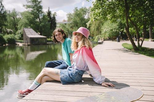 2 Women Sitting on Wooden Dock Near Lake