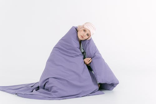 A Woman Covered With Purple Blanket