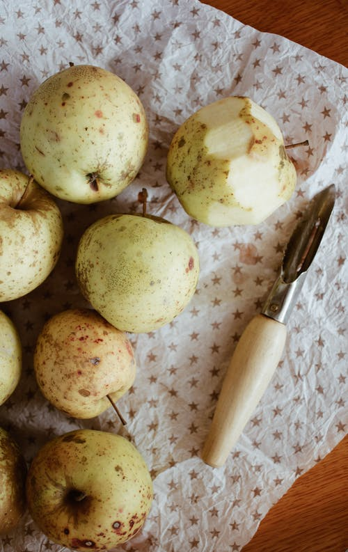 Fresh apples and peeler on paper at home