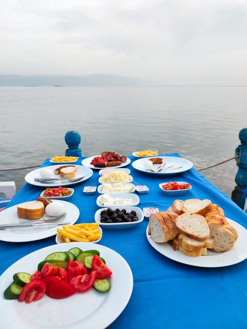 White Ceramic Plates With Food on Blue Tablecloth on Pier Near Water