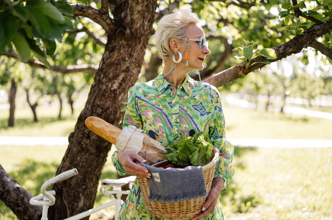Woman in Blue and White Floral Shirt Holding Brown Woven Basket