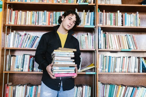 Woman in Black Long Sleeve Shirt Holding Books